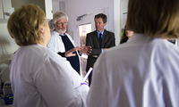 """Kristian Berg, head of the """"Lumiblast"""" project, giving prominent guests a tour of his lab (from RCN news article)."""